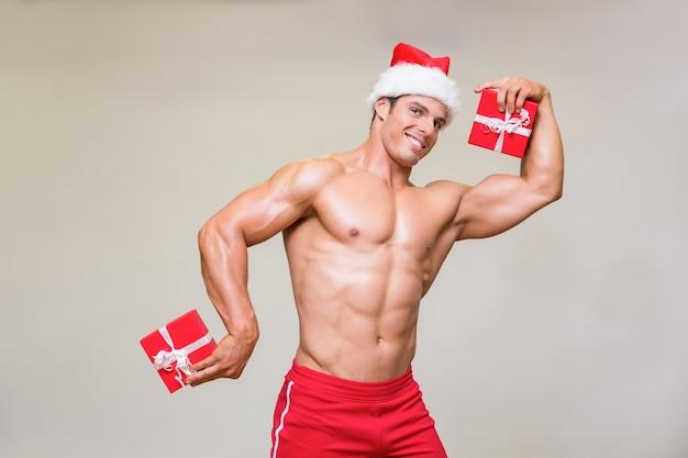 Homem macho sem camisa em presentes de santa holding