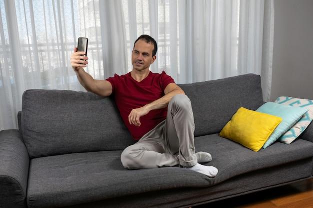 Homem maduro (44 anos) sentado no sofá usando meias e tirando uma foto de si mesmo.