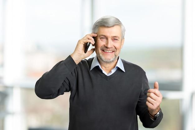 Homem maduro alegre com telefone. um retrato horizontal de homem maduro com cabelos grisalhos e rugas falando em smartphone, turva.