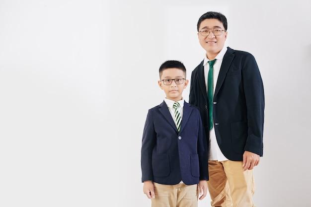 Homem maduro alegre e filho pré-adolescente posando em trajes formais, isolado no branco