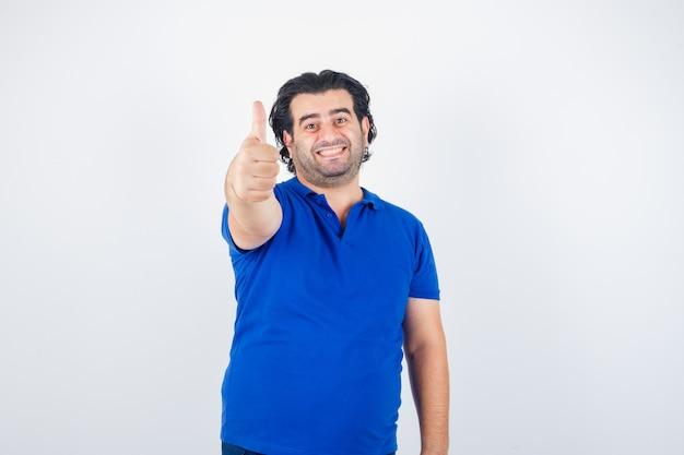 Homem maduro aparecendo o polegar em uma camiseta azul, jeans e parecendo feliz, vista frontal.