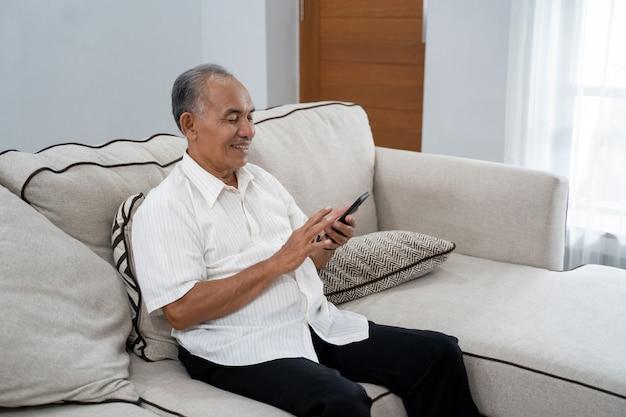 Homem maduro asiático usando telefone celular