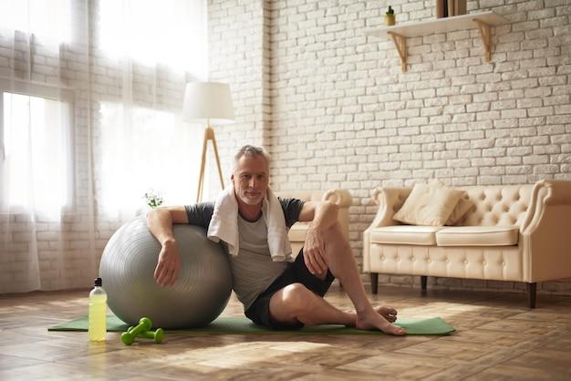 Homem maduro ativo na recuperação de treino de bola de ajuste.