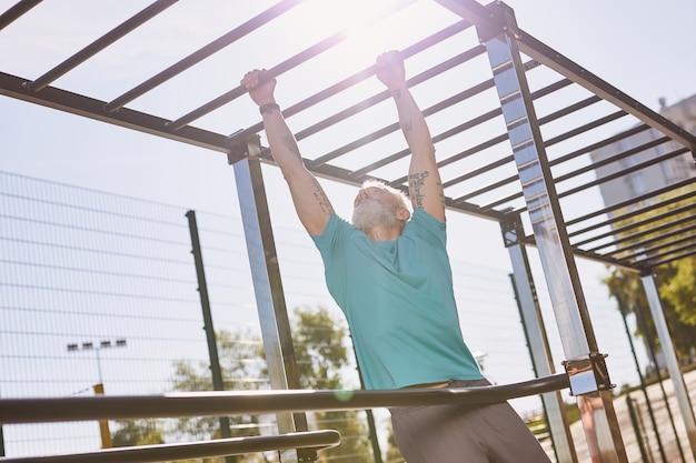 Homem maduro atlético de treino de manhã cedo em boa forma escalando barras de macaco fazendo flexões em