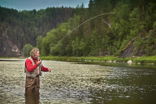 Homem maduro barbudo branco molhado está parado na água no meio do rio e pesca pesca com mosca, turismo ecológico.