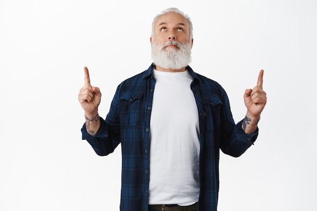 Homem maduro, barbudo, caucasiano, olhando para cima, apontando os dedos acima para mostrar um anúncio, lendo um texto promocional na parte superior do espaço de cópia, em pé sobre uma parede branca