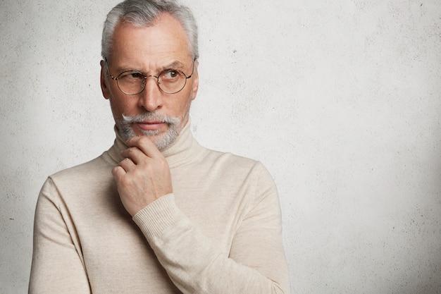 Homem maduro barbudo contemplativo em óculos