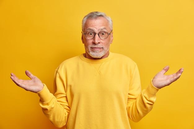 Homem maduro, barbudo e hesitante, perplexo, encolhe os ombros em espanto, espalha as mãos e olha com incerteza, veste um suéter casual isolado sobre a parede amarela, toma decisões ou escolhe