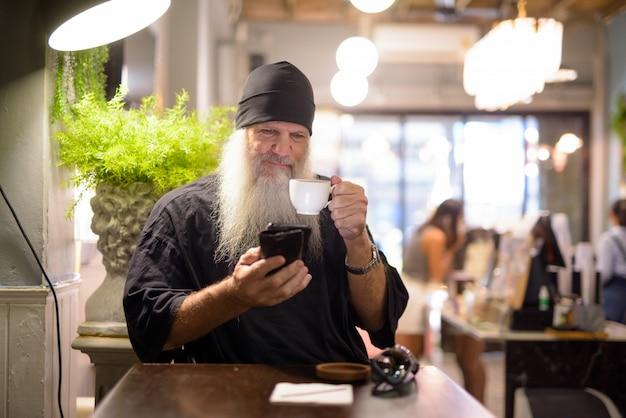 Homem maduro barbudo hippie bebendo café e usando o telefone na cafeteria
