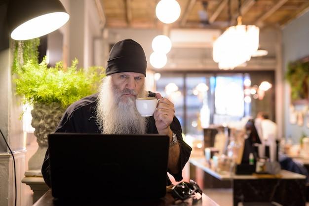 Homem maduro barbudo hippie bebendo café enquanto usa o laptop na cafeteria