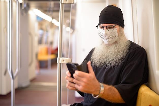 Homem maduro barbudo hippie com máscara, usando o telefone e sentado dentro do trem