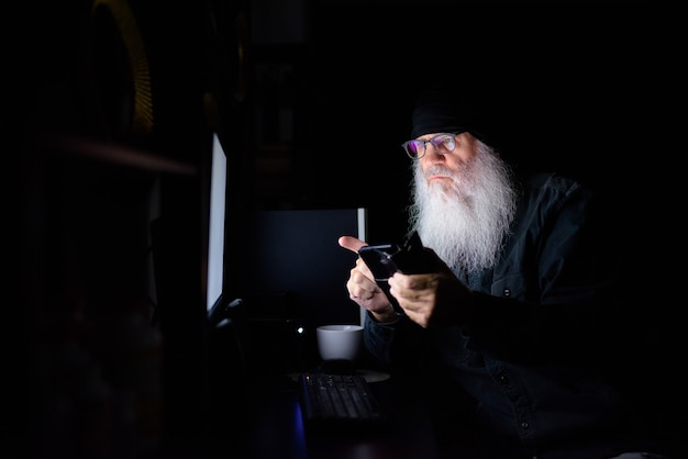 Homem maduro barbudo hippie usando o telefone enquanto trabalhava horas extras em casa à noite