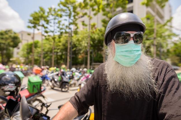 Homem maduro barbudo hipster com óculos de sol e máscara pensando enquanto andava de moto