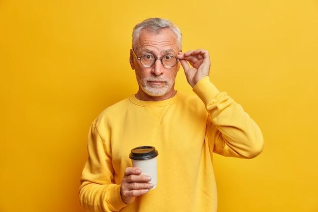 Homem maduro barbudo surpreso mantém a mão sobre os óculos, bebidas, café para viagem ouve notícias surpreendentes, usa um macacão casual isolado sobre a parede amarela