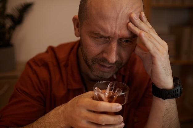 Homem maduro bêbado, bebendo álcool e se livrando de seus problemas dessa forma