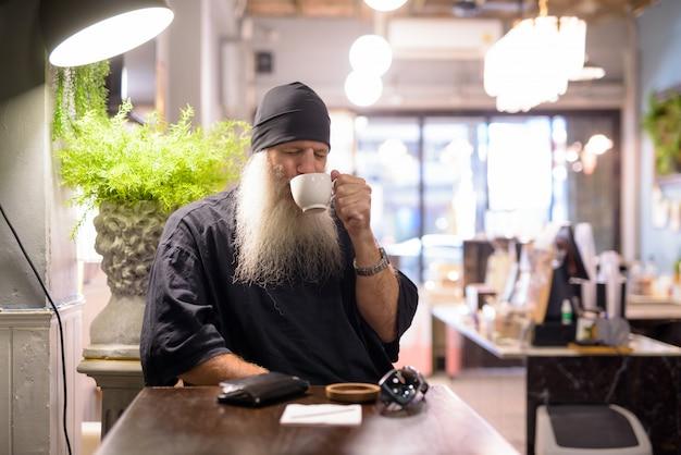 Homem maduro bonito barbudo hippie bebendo café e sentado na cafeteria