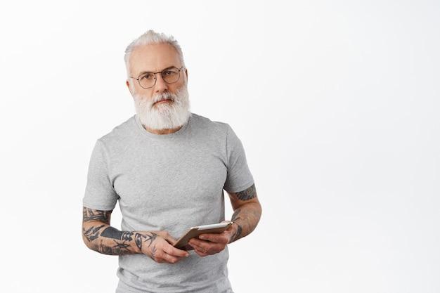 Homem maduro bonito com barba grisalha e tatuagens, usando óculos e lendo em tablet digital, usando dispositivo para navegação na internet, em pé com uma camiseta casual contra uma parede branca