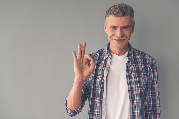 Homem maduro bonito em roupas casuais está mostrando sinal de ok