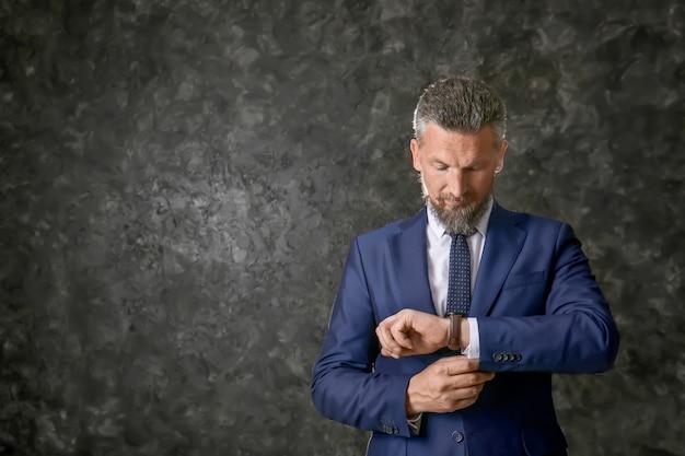 Homem maduro bonito em um terno elegante usando relógio de pulso em fundo escuro texturizado