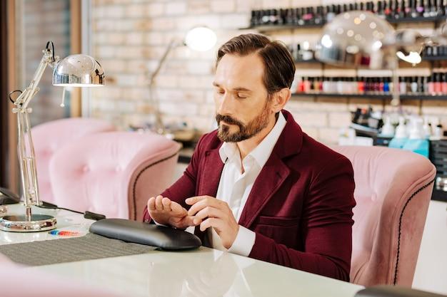 Homem maduro bonito examinando manicure e sentado