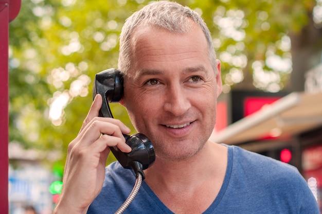 Homem maduro bonito falando no telefone em uma cabine telefônica