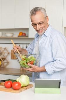 Homem maduro bonito parado na cozinha cozinhar salada.