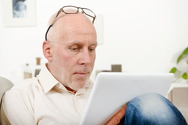 Homem maduro bonito usando tablet
