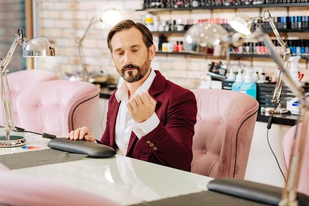 Homem maduro calmo avaliando manicure e sentado