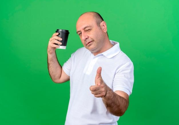 Homem maduro casual piscando segurando uma xícara de café e mostrando um gesto isolado na parede verde
