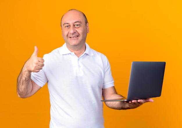 Homem maduro casual sorridente segurando uma pasta com o polegar isolado na parede amarela