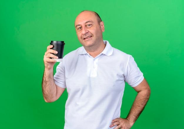 Homem maduro casual sorridente segurando uma xícara de café e colocando a mão no quadril isolado na parede verde
