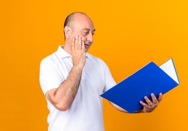 Homem maduro casual surpreso segurando e olhando para a pasta e colocando a mão na bochecha isolada na parede amarela