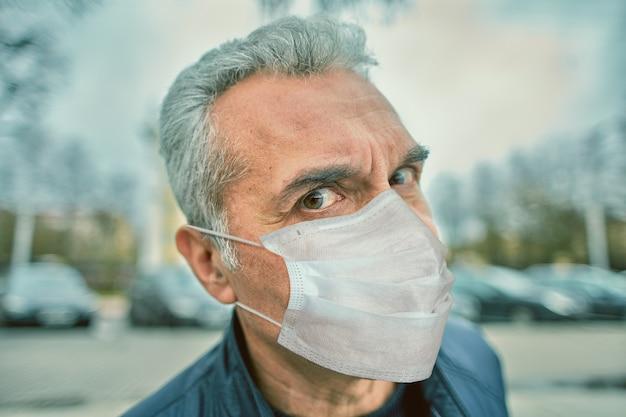 Homem maduro, caucasiano, com máscara cirúrgica facial protetora descartável