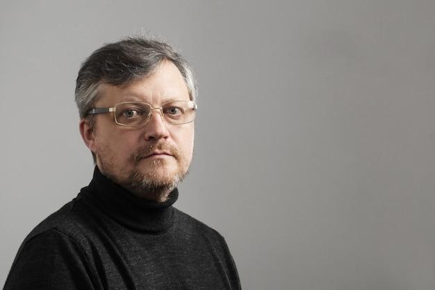 Homem maduro com barba em fundo cinza