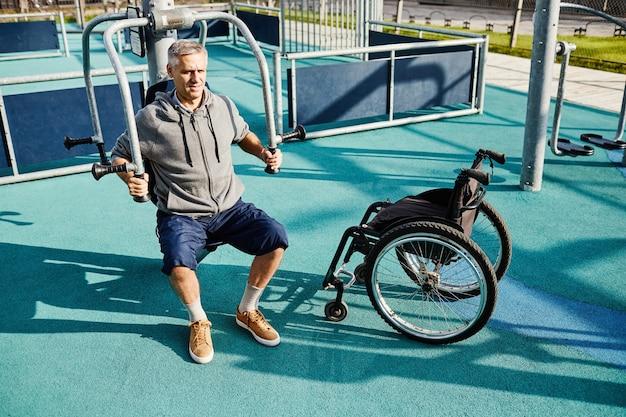 Homem maduro com deficiência fazendo exercícios em equipamentos para fortalecê-lo durante sua reabilitação ...