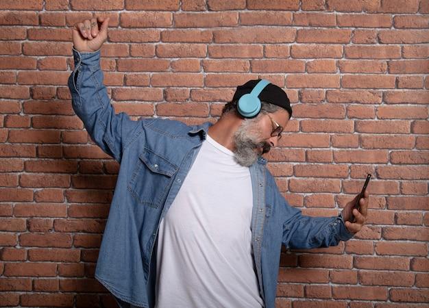 Homem maduro com fones de ouvido, ouvindo música no celular. homem maduro se divertindo com as novas tendências de tecnologia - conceito de tecnologia.