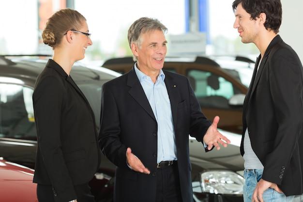 Homem maduro com jovem casal e automóveis na concessionária