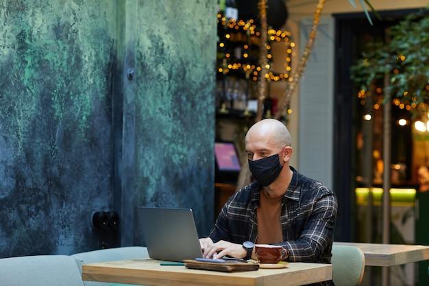 Homem maduro com máscara protetora, digitando no laptop enquanto está sentado à mesa, trabalhando online em um café durante a pandemia