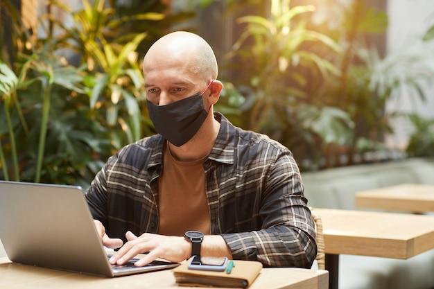 Homem maduro com máscara protetora sentado à mesa e trabalhando em um laptop no café