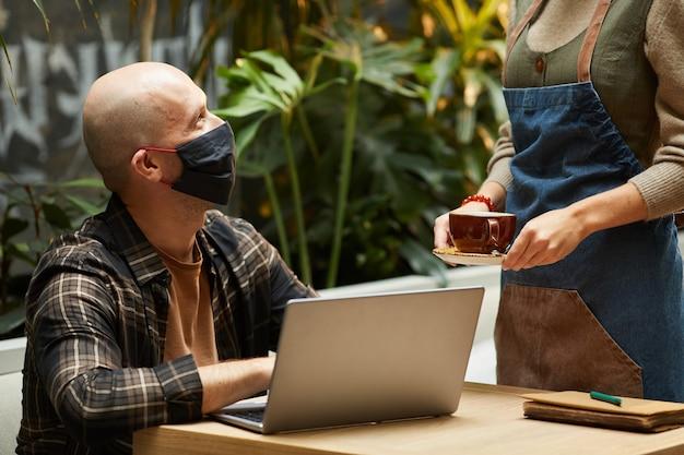 Homem maduro com máscara protetora, trabalhando à mesa com o laptop, enquanto o garçom serve o café no restaurante