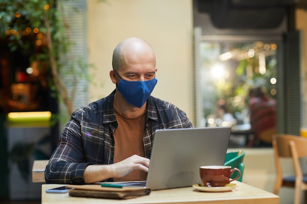 Homem maduro com máscara protetora trabalhando online em um laptop enquanto está sentado em uma cafeteria
