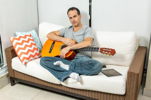 Homem maduro com os braços na guitarra e sentado no sofá.