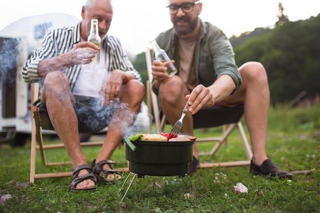 Homem maduro com pai sênior, falando no acampamento ao ar livre, churrasco na viagem de férias da caravana.