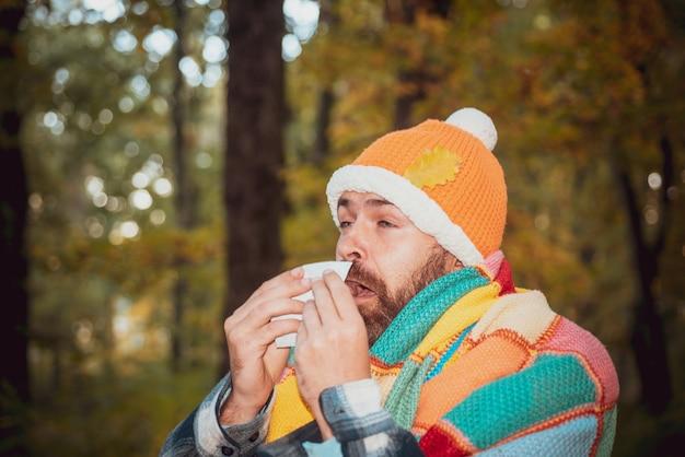 Homem maduro com paletó sofrendo de assoar o nariz de frio com um lenço de papel parecendo infeliz muito ...
