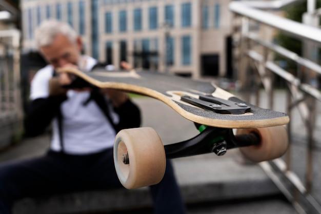 Homem maduro com skate de mobilidade sustentável
