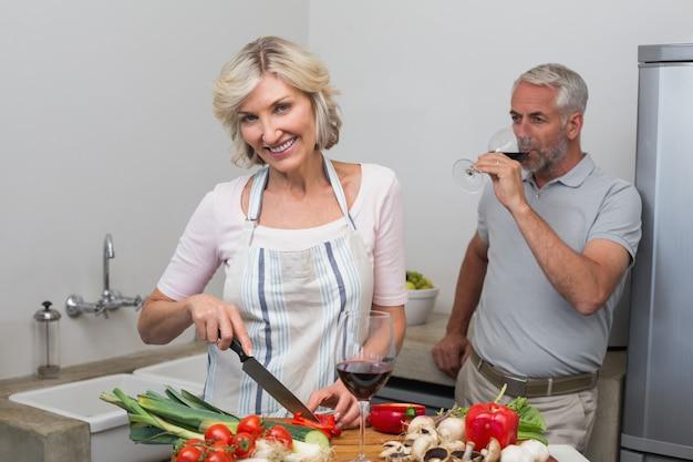 Homem maduro, com, vidro vinho, e, mulher, legumes chopping, em, cozinha