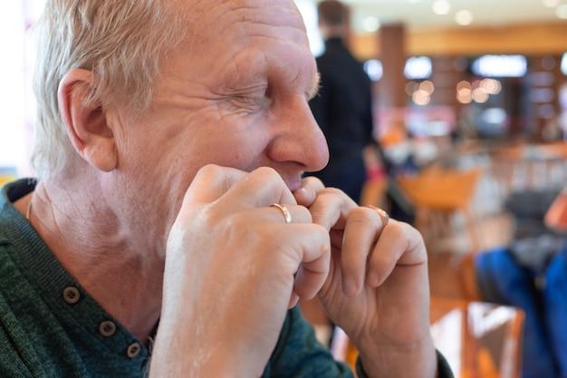 Homem maduro comendo comida com as mãos em um café, fechando os olhos