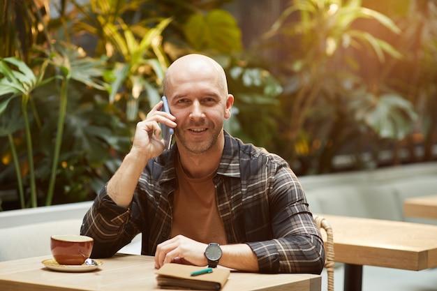 Homem maduro conversa no celular, sorrindo, sentado à mesa de um café