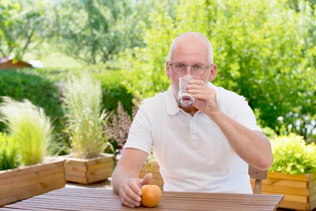 Homem maduro, copo de água no terraço do jardim
