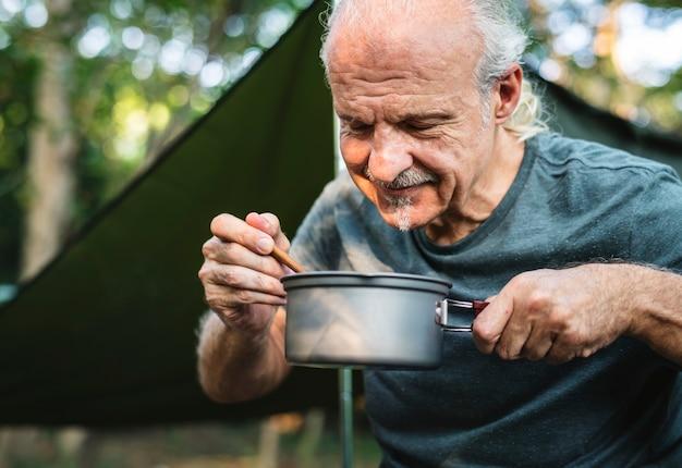 Homem maduro, cozinhar, em, um, campsite
